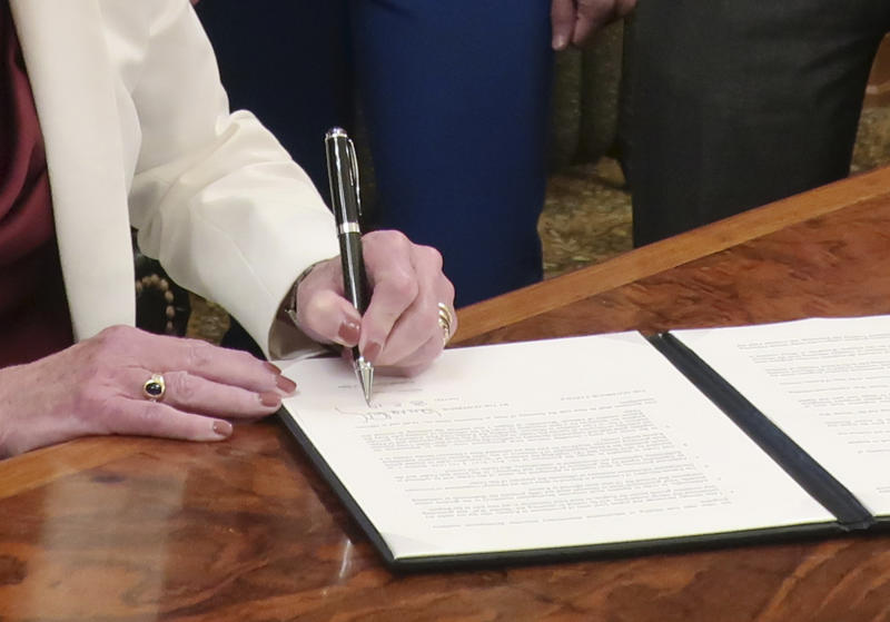 """Kansas Gov. Laura Kelly signs an executive order aimed at ending an economic """"border war"""" between her state and Missouri over jobs in the Kansas City area, Friday, Aug. 2, 2019, at the Statehouse in Topeka, Kansas. The states are promising not to use their incentives to lure existing businesses across their border in the area but the issue of local government incentives has not been fully resolved. (AP Photo/John Hanna)"""