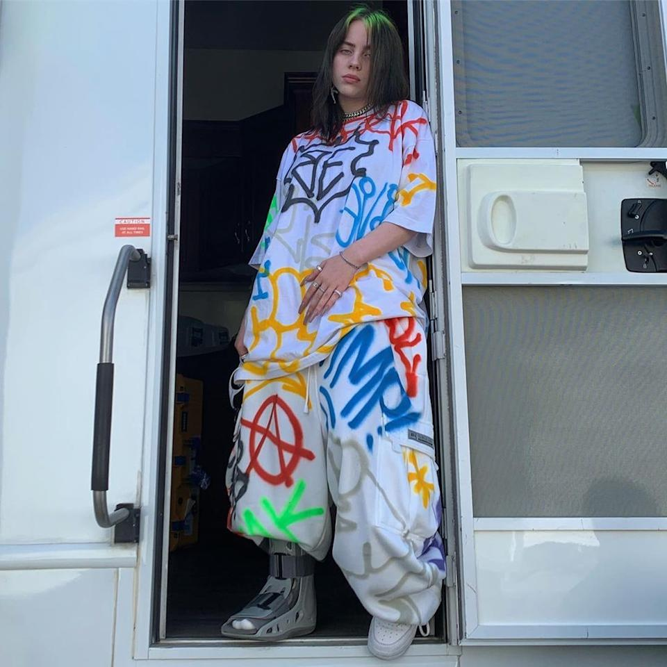"""In true Billie Eilish style, the artist went with an oversized shirt and matching shorts for a performance, but this time, the graphics featured the initials of her name. In addition to the stylish, and brightly colored choice of backstage outfit — which is part of <a href=""""https://www.teenvogue.com/story/billie-eilish-capsule-collection-freak-city?mbid=synd_yahoo_rss"""">the capsule collection</a> she designed for Freak City — she also used the image to send a message to fans about her choice of wardrobe. Billie shared the photo of herself on Instagram and <a href=""""https://www.instagram.com/p/B2db7LRFLJ/"""">writing</a>, """"If only i dressed normal id be so much hotter yeah yeah come up with a better comment im tired of that one."""" The comment was clearly directed at those who continue to pick apart her clothing, and as the singer has explained, she <a href=""""https://www.teenvogue.com/story/billie-eilish-is-being-sexualized-because-of-a-tank-top?mbid=synd_yahoo_rss"""">chooses oversized items</a> so as to prevent unwanted commentary on her body."""