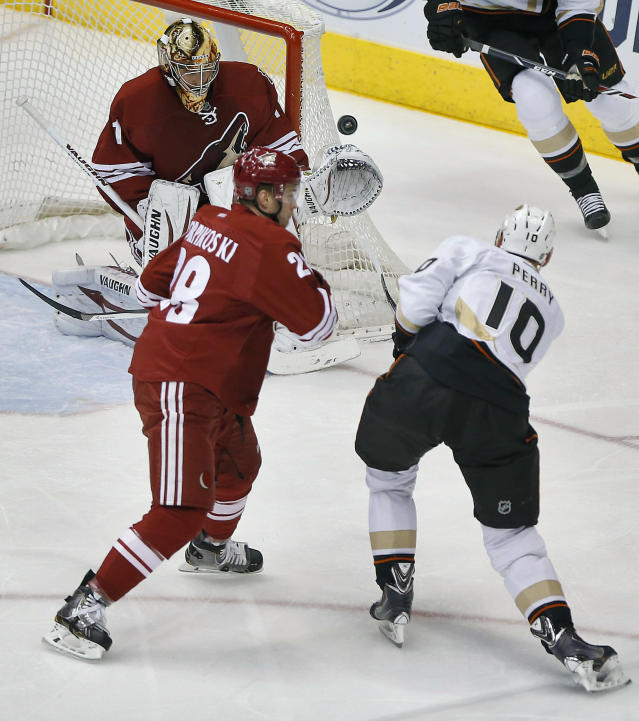 Anaheim Ducks' Corey Perry (10) shoots on Phoenix Coyotes goalie Thomas Greiss (1) as Coyotes' Lauri Korpikoski defends during the second period of an NHL hockey game, Saturday, Jan. 11, 2014, in Glendale, Ariz. (AP Photo/Matt York)