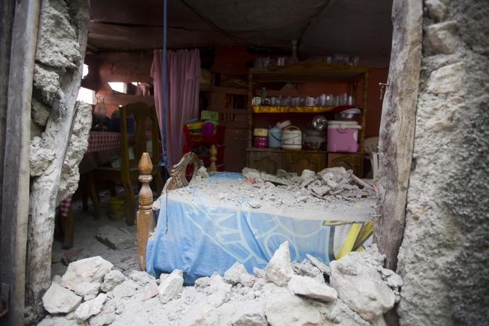 A bed is covered in rubble caused by a magnitude 5.9 earthquake the night before, in Gros Morne, Haiti, Sunday, Oct. 7, 2018. Emergency teams worked to provide relief in Haiti on Sunday after the quake killed at least 11 people and left dozens injured. ( AP Photo/Dieu Nalio Chery)