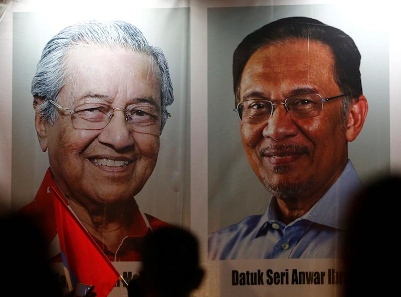 People pass posters of Malaysian Prime Minister Tun Dr Mahathir Mohamad and Datuk Seri Anwar Ibrahim at a rally in Kuala Lumpur May 16, 2018. — Reuters pic