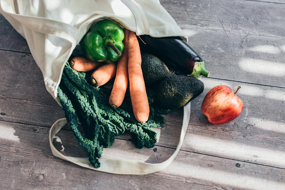 Close-up shot of a tote bag with various vegetables on a wooden table.