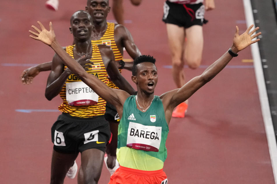Selemon Barega, of Ethiopia, celebrates after winning the men's 10,000-meter run at the 2020 Summer Olympics, Friday, July 30, 2021, in Tokyo. (AP Photo/Charlie Riedel)