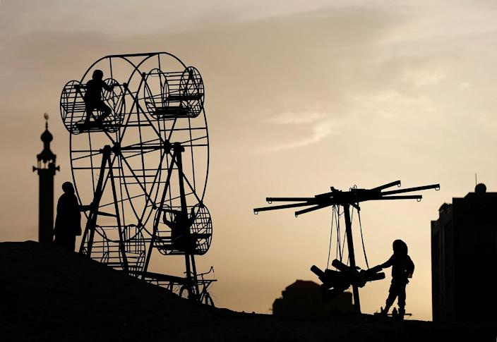 <p>Afghan children play on a manually operated Ferris wheel in Kabul, Afghanistan, April 11, 2017. (Mohammad Ismail/Reuters) </p>