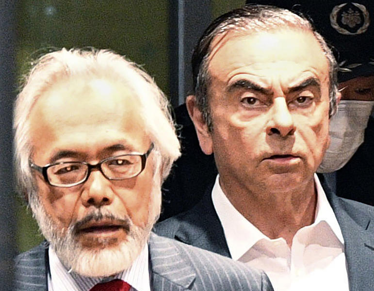 "FILE - In this April 25, 2019, file photo, former Nissan Chairman Carlos Ghosn, right, walks behind his lawyer Takashi Takano as he leaves the Tokyo Detention Center in Tokyo. Takano said Saturday, Jan. 4, 2020, he felt outraged and betrayed by his client's escape from Japan to Lebanon, but also expressed an understanding for his feelings of not being able to get a fair trial. ""My anger gradually began to turn to something else,""  Takano wrote in his blog post. (Kyodo News via AP, File)/Kyodo News via AP)"