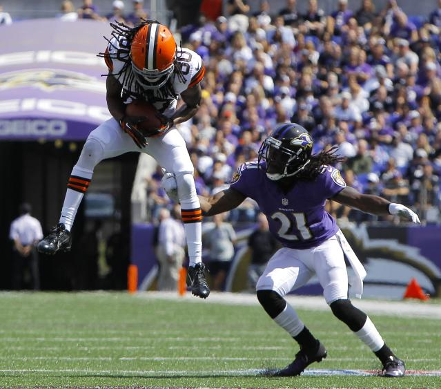 Cleveland Browns wide receiver Travis Benjamin (L) hauls in a first down pass against Baltimore Ravens cornerback Lardarius Webb (R) in the first half of their NFL football game in Baltimore September 15, 2013. REUTERS/Gary Cameron (UNITED STATES - Tags: SPORT FOOTBALL TPX IMAGES OF THE DAY)