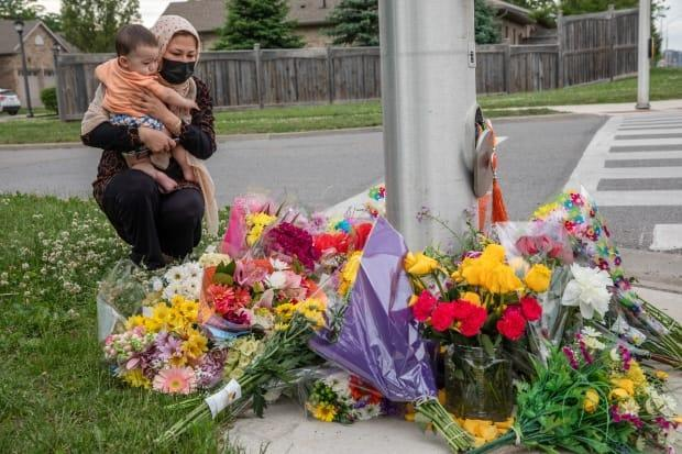 A mourner brings flowers to the spot in London, Ont., where four members of a Muslim family were run down and killed in what police say was a hate-motivated attack. London Mayor Ed Holder and Quebec City Mayor Regis Labeaume are jointly calling for a national summit on Islamophobia. (Brett Gundlock/The Canadian Press - image credit)