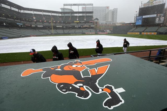 Members of the Baltimore Orioles walk into the dugout for shelter from the rain before a scheduled baseball game between the Orioles and the Pittsburgh Pirates, Tuesday, April 29, 2014, in Baltimore. Officials postponed the game due to the rain, and it has been rescheduled for Thursday. (AP Photo/Patrick Semansky)
