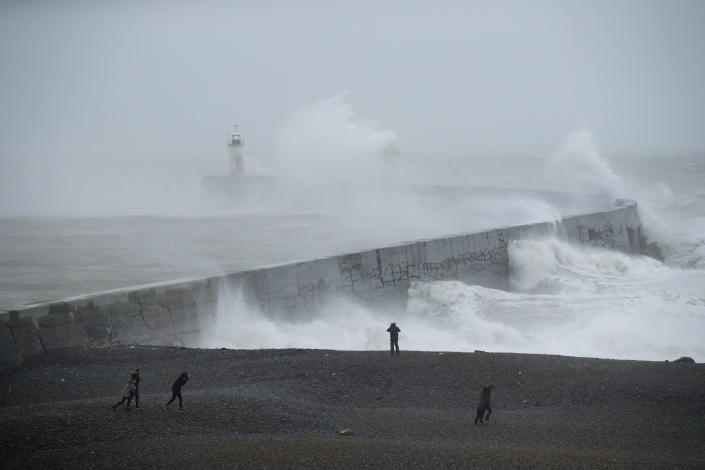 Waves crash over the harbour wall by a lighthouse as Storm Ciara hits Newhaven, on the south coast of England, Sunday, Feb. 9, 2020. Trains, flights and ferries have been cancelled and weather warnings issued across the United Kingdom and in northern Europe as the storm with winds expected to reach hurricane levels batters the region. (AP Photo/Matt Dunham)