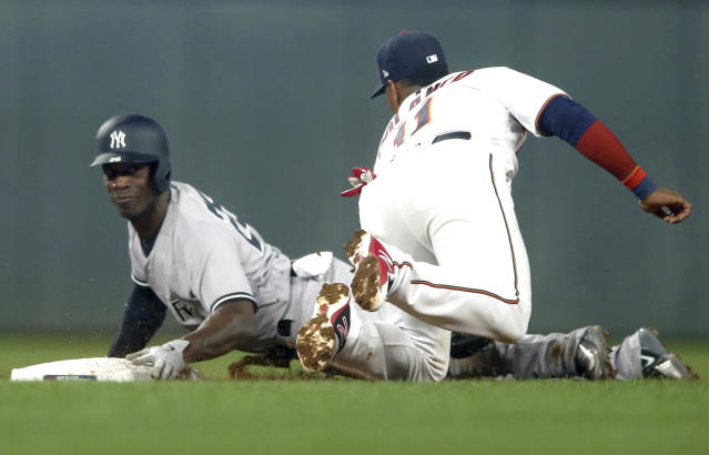 New York Yankees' Andrew McCutchen, left, is tagged out by Minnesota Twins shortstop Jorge Polanco as he attempted to steal second in the third inning of a baseball game Tuesday, Sept. 11, 2018, in Minneapolis. (AP Photo/Jim Mone)