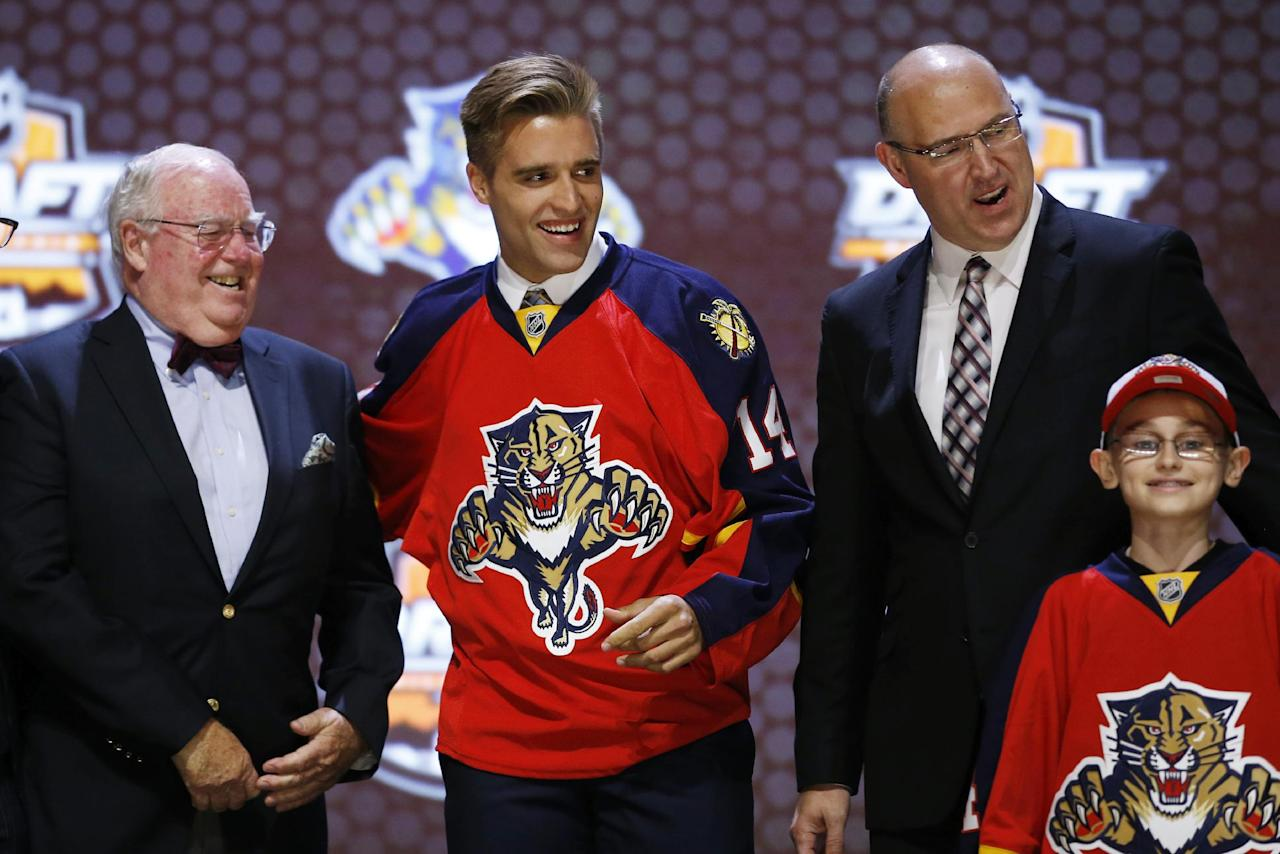Aaron Ekblad stands with Florida Panthers officials after being chosen first overall during the first round of the NHL hockey draft, Friday, June 27, 2014, in Philadelphia. (AP Photo/Matt Slocum)