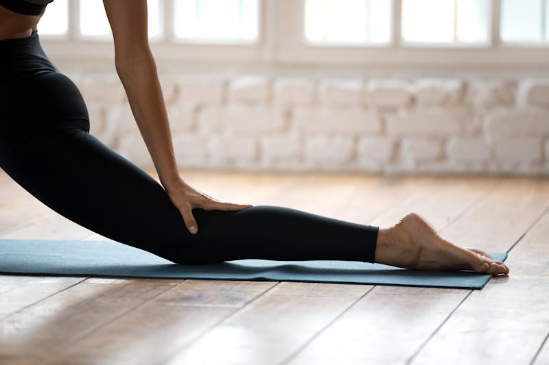 Sporty yogi woman practicing yoga, doing Horse rider exercise, anjaneyasana pose, working out, wearing sportswear, black pants, close up, yoga studio, well being, leg stretching and flexibility concept