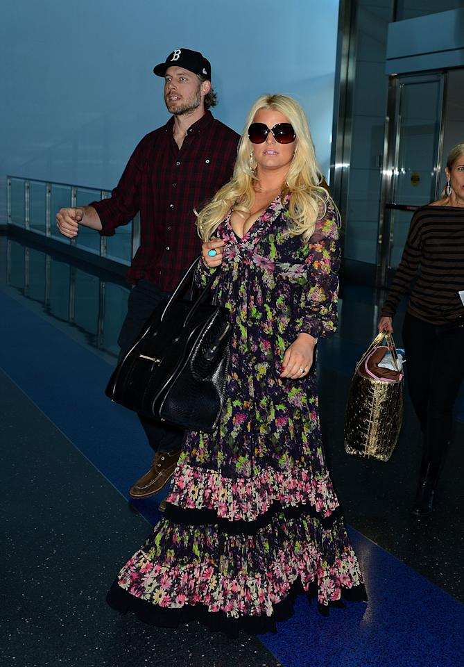 "<div class=""caption-credit""> Photo by: Getty Images</div><div class=""caption-title""></div>Tray table is certainly in its upright position! Jessica Simpson's modest look at JFK in September 2012 is offset by her aggressive cleavage."