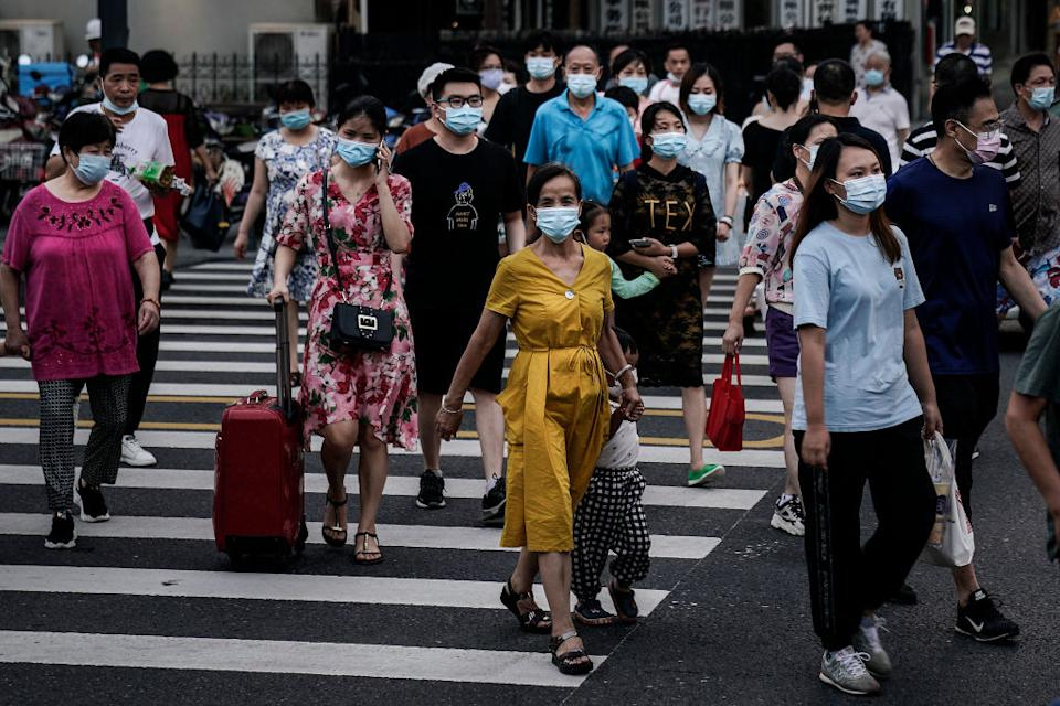 People cross the street wearing surgical masks.