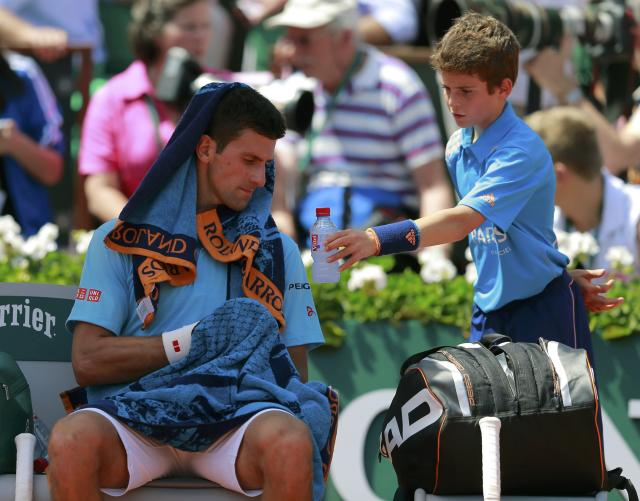 A ball boy gives a bottle of water to Novak Djokovic of Serbia during a break in his men's semi-final match against Ernests Gulbis of Latvia at the French Open tennis tournament at the Roland Garros stadium in Paris June 6, 2014. REUTERS/Vincent Kessler (FRANCE - Tags: SPORT TENNIS)