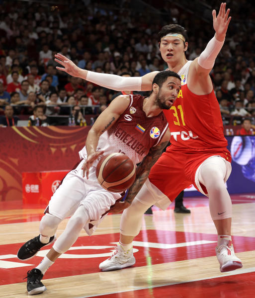 Heissler Guillent of Venezuela drives past Wang Zhelin of China during their group phase game in the FIBA Basketball World Cup at the Cadillac Arena in Beijing, Wednesday, Sept. 4, 2019. (AP Photo/Mark Schiefelbein)