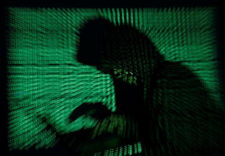 Hooded an holds laptop computer as cyber code is projected on him in this illustration picture