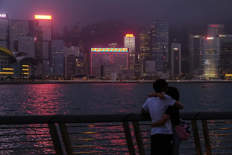 A couple across from illuminated skyscrapers on Victoria Harbor in Hong Kong on May 28, 2020. | Roy Liu—Bloomberg/Getty Images.