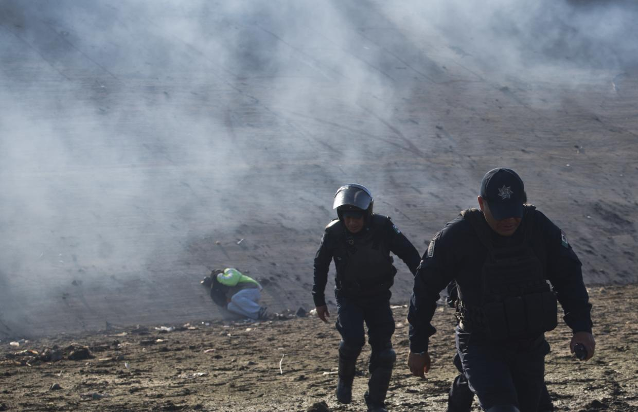 A Honduran migrant lies on the riverbank as Mexican police move away from tear gas fired by U.S. agents at the Mexico-U.S. border in Tijuana, Mexico, Sunday, Nov. 25, 2018, as a group of migrants try to pressure their way into the U.S. (Photo: Ramon Espinosa/AP)