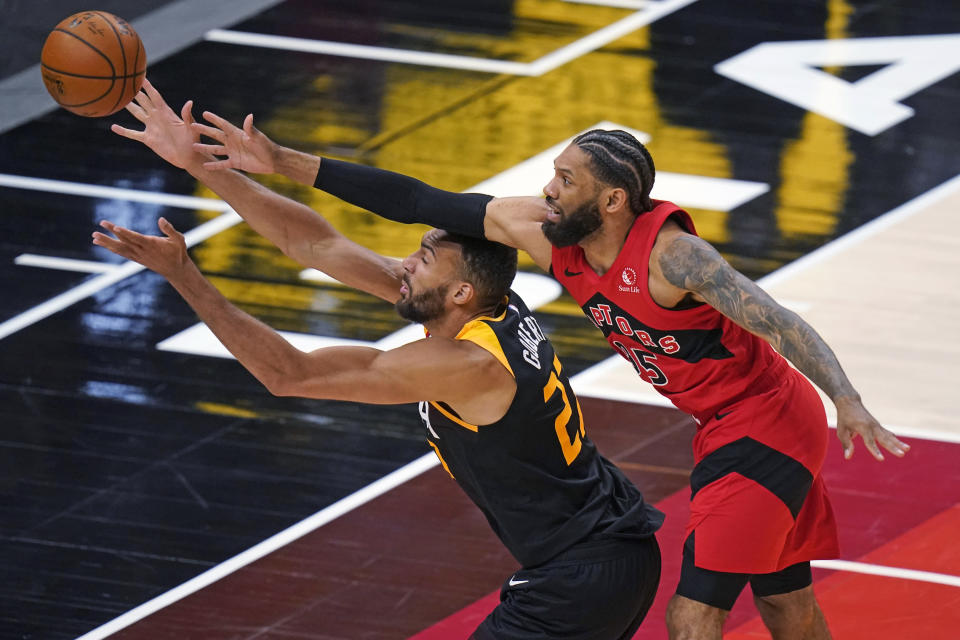 Toronto Raptors guard DeAndre' Bembry, right, and Utah Jazz center Rudy Gobert (27) reach for the ball during the second half of an NBA basketball game Saturday, May 1, 2021, in Salt Lake City. (AP Photo/Rick Bowmer)