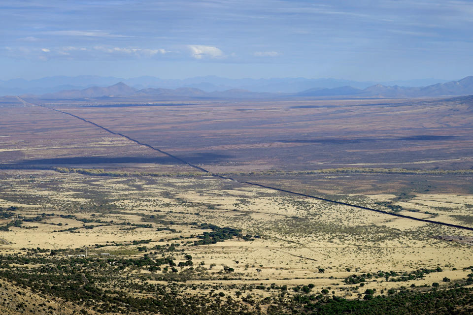 With Mexico to the right, the border wall cuts through the Sonoran Desert, Wednesday, Dec. 9, 2020, as seen from atop Montezuma's Pass in Coronado National Memorial, in Hereford, Ariz. Construction of the border wall, mostly in government owned wildlife refuges and Indigenous territory, has led to environmental damage and the scarring of unique desert and mountain landscapes that conservationists fear could be irreversible. (AP Photo/Matt York)