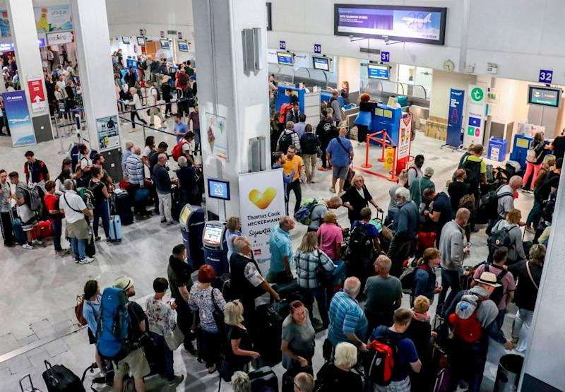 Tourists wait at a Thomas Cook company counter at Heraklion airport on the island of Crete on Sept. 23.