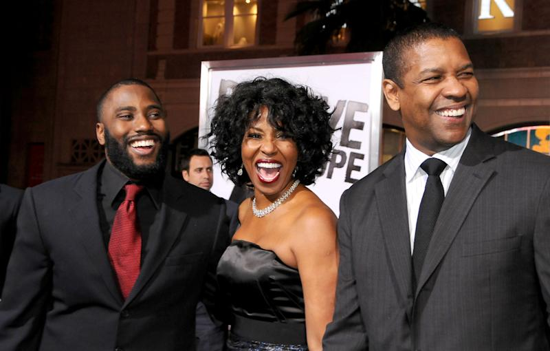 "HOLLYWOOD, CA - JANUARY 11: John David Washington, Pauletta Washington and Denzel Washington arrive at ""The Book Of Eli"" Los Angeles Premiere at Grauman's Chinese Theater on January 11, 2010 in Hollywood, California. (Photo by Gregg DeGuire/FilmMagic)"