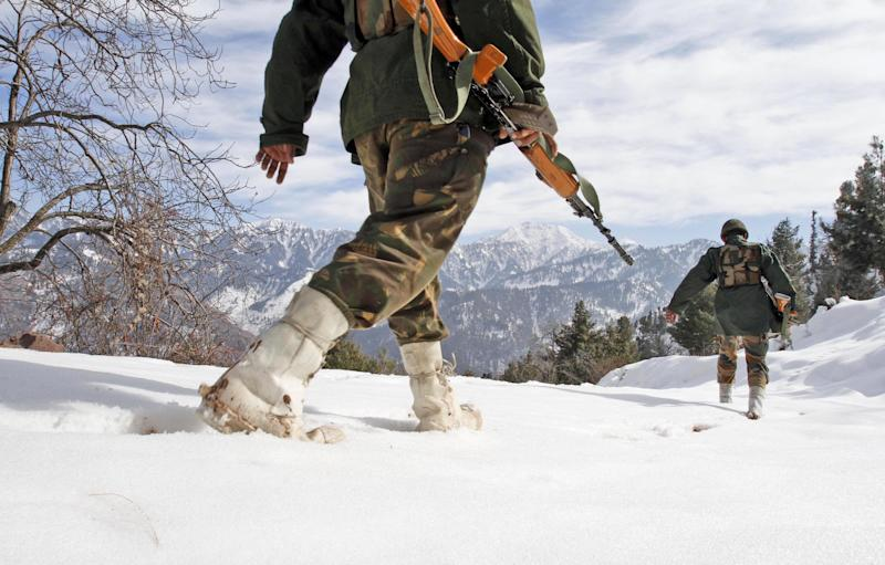 """Indian army soldiers patrol near the Line of Control (LOC), the line that divides Kashmir between India and Pakistan, in Churunda village, about 150 Kilometers (94 miles) northwest of Srinagar, India, Tuesday, Jan. 15, 2013. India's relations with archrival Pakistan """"cannot be business as usual"""" in the wake of a spate of attacks in Kashmir, Prime Minister Manmohan Singh said Tuesday in a statement that threatens to ratchet up tensions in the wake of the Himalayan violence. A series of tit-for-tat attacks, including the beheading of an Indian soldier, across the LOC that divides the Himalayan region has killed two Pakistani and two Indian soldiers over the past 10 days. (AP Photo/Mukhtar Khan)"""