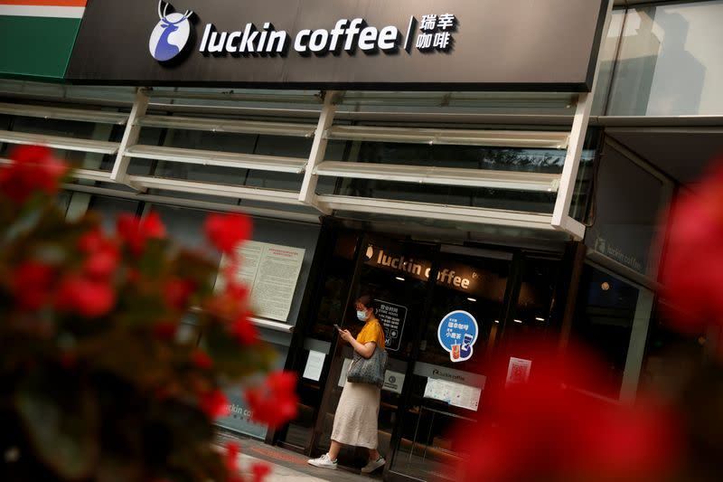 A woman leaves a store of the Chinese coffee house chain Luckin Coffee in Beijing