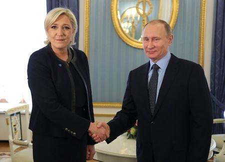 Russian President Putin shakes hands with French far-right party leader Le Pen during their meeting in Moscow