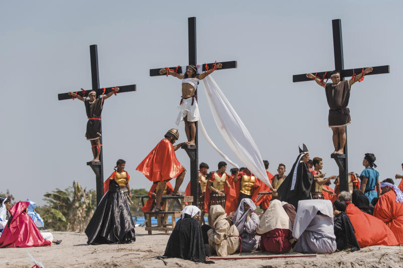 Ruben Enaje, center, dressed as Jesus, is seen nailed on cross for the 33rd year in a row during a reenactment of Jesus Christ's sufferings as part of Good Friday rituals in the village of San Pedro Cutud, Pampanga province, northern Philippines. Friday, April 19, 2019. Over a thousand Filipino Roman Catholic devotees and tourists flocked to a farming village north of Manila on Friday to witness the crucifixion of several devotees in a costumed reenactment of Jesus Christ's sufferings, a gory annual tradition church leaders frown upon. (AP Photo/Iya Forbes)