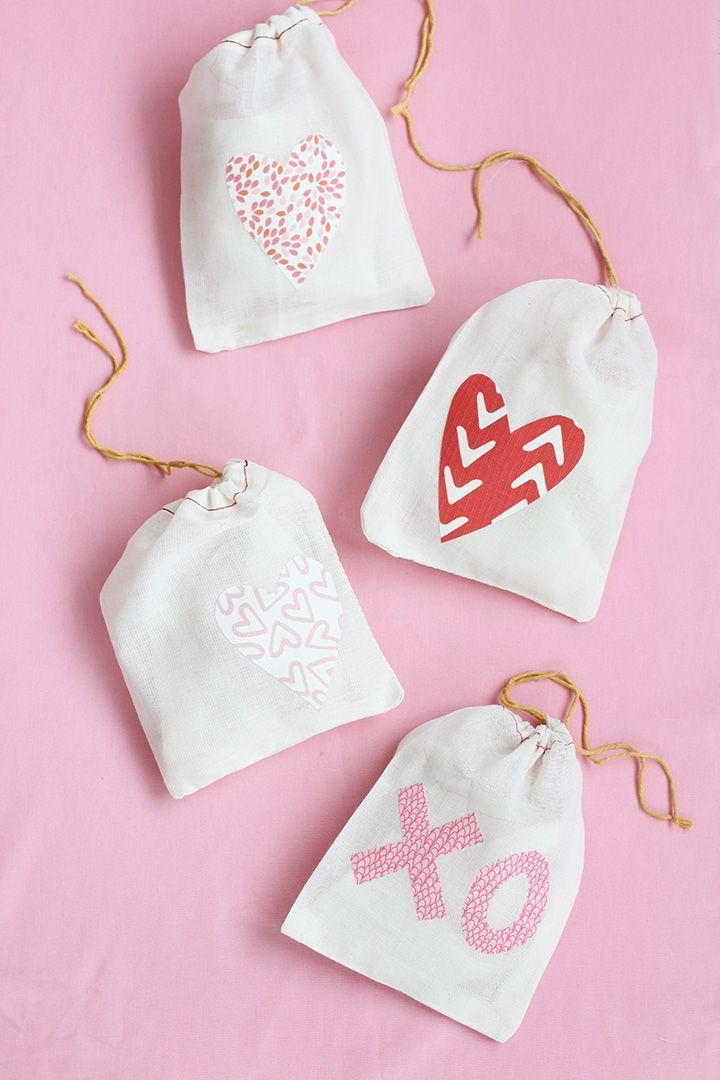 """<p>Pass out sweets — hugs and kisses too! — in these adorable goodie bags. </p><p><a class=""""link rapid-noclick-resp"""" href=""""https://www.amazon.com/Tatuo-Pieces-Drawstring-Wedding-Supplies/dp/B07GTFJ514/?tag=syn-yahoo-20&ascsubtag=%5Bartid%7C10055.g.2020%5Bsrc%7Cyahoo-us"""" rel=""""nofollow noopener"""" target=""""_blank"""" data-ylk=""""slk:SHOP MUSLIN BAGS"""">SHOP MUSLIN BAGS</a></p><p><em><a href=""""https://www.aliceandlois.com/valentine-treat-bags/"""" rel=""""nofollow noopener"""" target=""""_blank"""" data-ylk=""""slk:Get the tutorial at Alice & Lois »"""" class=""""link rapid-noclick-resp"""">Get the tutorial at Alice & Lois »</a></em><br></p>"""