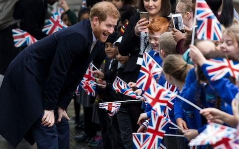 Prince Harry beams as he chats to children in Birmingham - Credit: Heathcliff O'Malley for The Telegraph