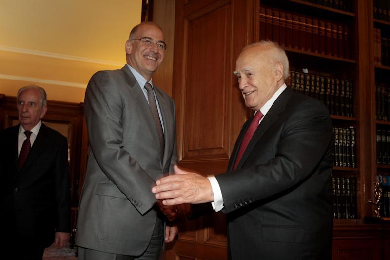 Greek President Karolos Papoulias, right, welcomes minister of public order Nikos Dendias, at the presidential palace in Athens, Tuesday, Sept. 24, 2013. Authorities said the police's internal affairs division were searching the precincts at Nikea and two other nearby locations after the government ordered an emergency inquiry into activities of the far-right Golden Dawn party and alleged ties to law enforcement officials.(AP Photo/Fosphotos/Panagiotis Tzamaros)