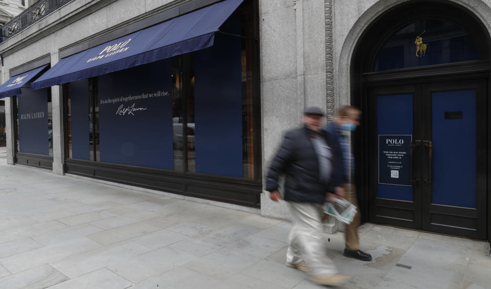 Men walk by a closed Ralph Lauren store in London, Thursday, July 16, 2020. Unemployment across the U.K. has held steady during the coronavirus lockdown as a result of a government salary support scheme, but there are clear signals emerging that job losses will skyrocket over coming months. The Office for National Statistics said Thursday there were 649,000 fewer people, or 2.2%, on payroll in June when compared with March when the lockdown restrictions were imposed. (AP Photo/Alastair Grant)