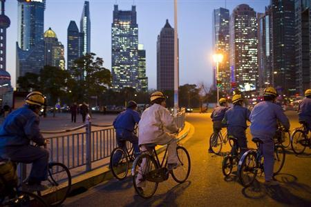 Construction workers ride along a street at central Shanghai