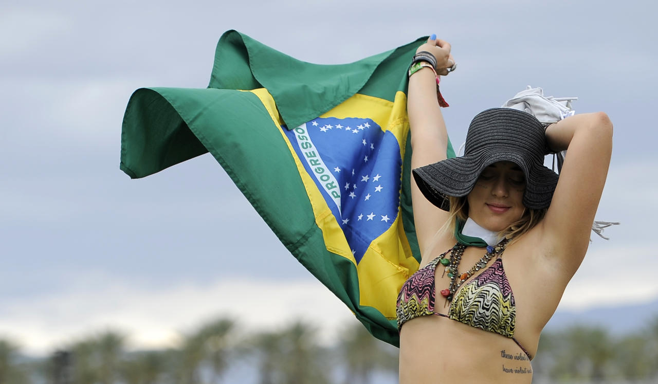 Marjorie Tavares, of Rio de Janeiro, Brazil, dances with a Brazilian flag during the first weekend of the 2012 Coachella Valley Music and Arts Festival, Friday, April 13, 2012, in Indio, Calif. (AP Photo/Chris Pizzello)
