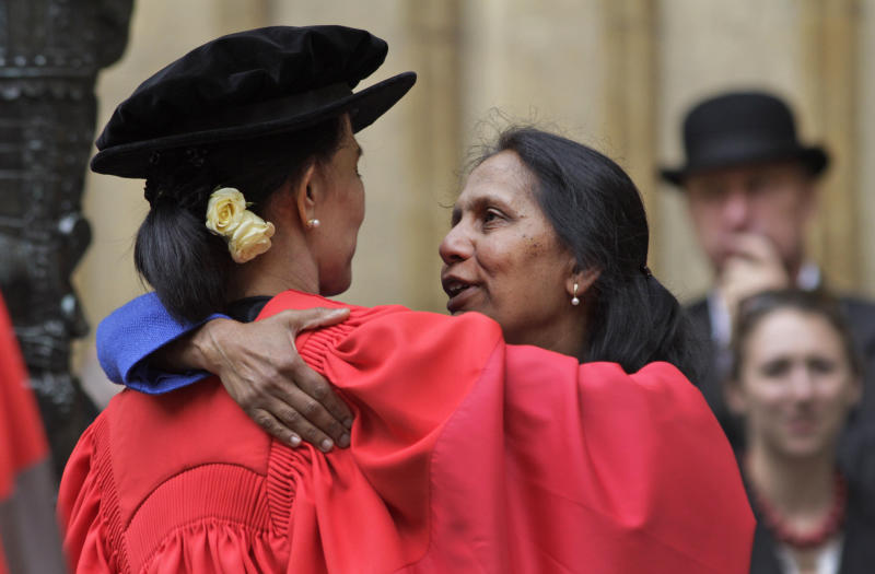 """A friend, name not available, embraces Myanmar opposition leader Aung San Suu Kyi, following an award ceremony at the Oxford University, Oxford, England, on Wednesday, June 20, 2012. It was a long wait, but Aung San Suu Kyi has finally received her honorary degree from Oxford University. In her speech, Suu Kyi praised the role Oxford played in helping her see humankind at its best during her long years under house arrest in Myanmar. """"The most important thing that I learned was respect for all of civilization,"""" she said, wearing a traditional red gown. """"In Oxford I learned to respect all that is best in human civilization. That helped me cope with something that was not quite the best."""" (AP Photo/Lefteris Pitarakis)"""