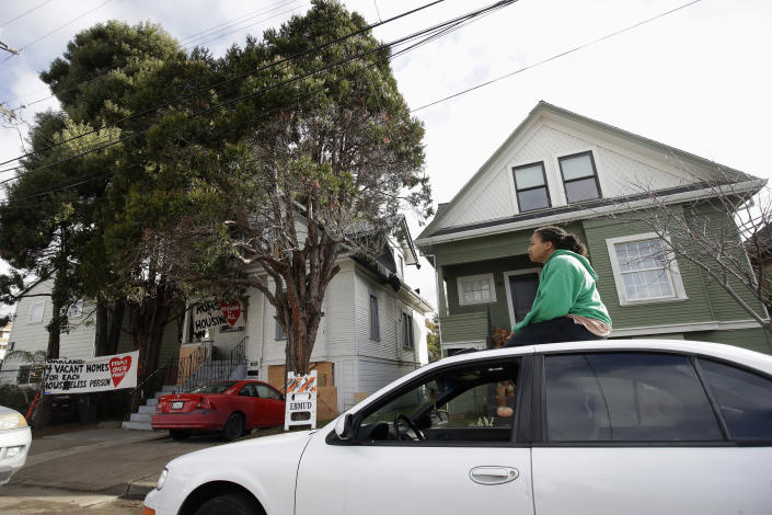 Sunday Simon, a supporter of homeless women who were occupying a house, sits on a car near the house, at left, in Oakland, Calif., Tuesday, Jan. 14, 2020. Homeless women ordered by a judge last week to leave a vacant house they occupied illegally in Oakland for two months have been evicted by sheriff's deputies. They removed two women and a male supporter Tuesday from the home before dawn in a case highlighting California's severe housing shortage and growing homeless population. (AP Photo/Jeff Chiu)