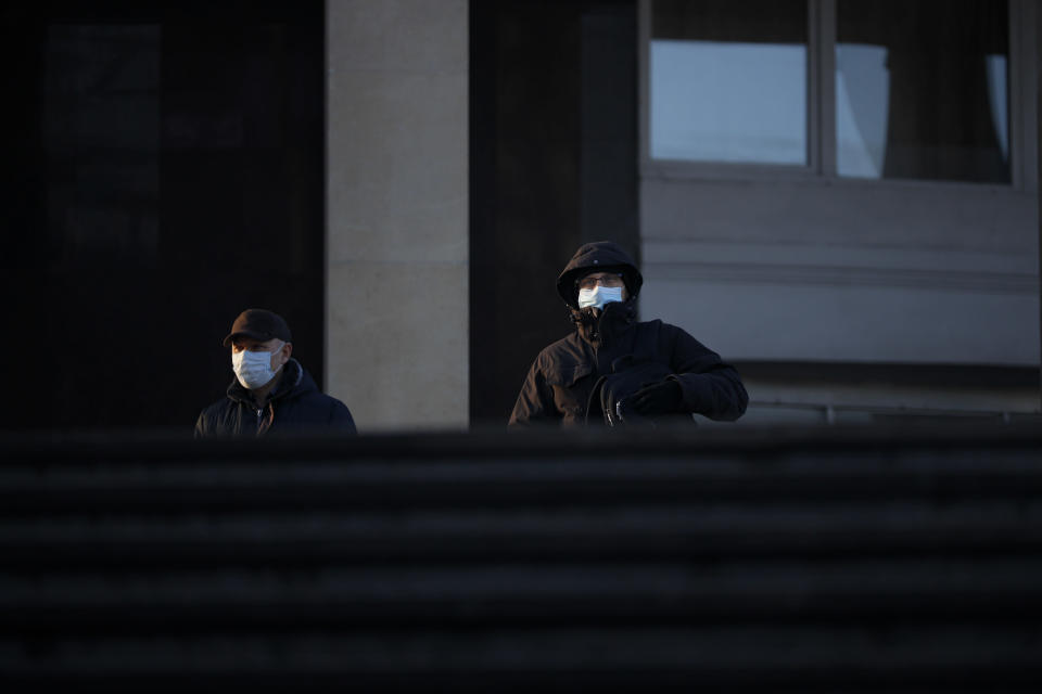 Two men wearing face masks to help curb the spread of the coronavirus walk into the underpass under the street during sunset in Moscow, Russia, Wednesday, Dec. 2, 2020. Russia has registered a record number of coronavirus deaths for a second straight day. Currently, there is a country-wide mask mandate and mostly mild restrictions that vary from region to region. (AP Photo/Alexander Zemlianichenko)