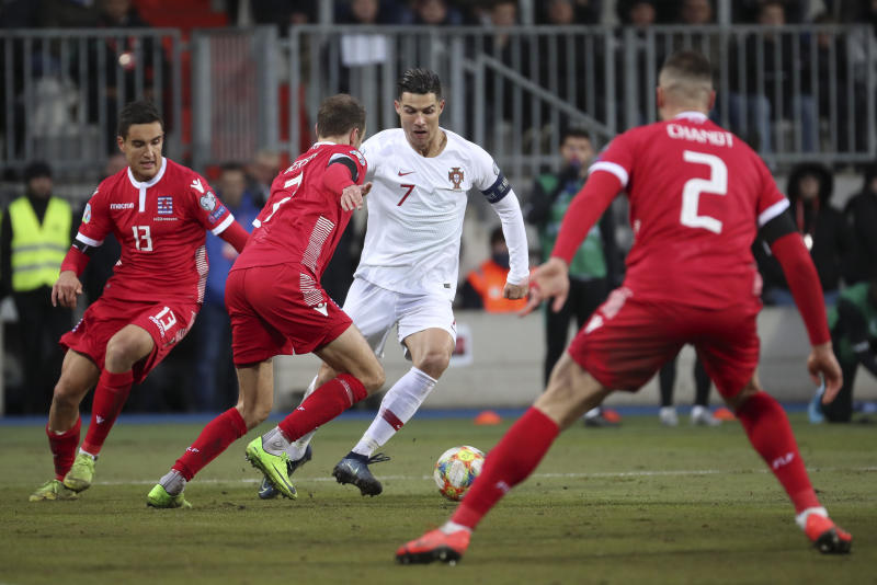 Portugal's Cristiano Ronaldo, third from left, fights for the ball with, from left, Luxembourg's Dirk Carlson, Luxembourg's Lars Gerson and Luxembourg's Maxime Chanot during the Euro 2020 group B qualifying soccer match between Luxembourg and Portugal at the Josy Barthel stadium in Luxembourg, Sunday, Nov. 17, 2019. (AP Photo/Francisco Seco)