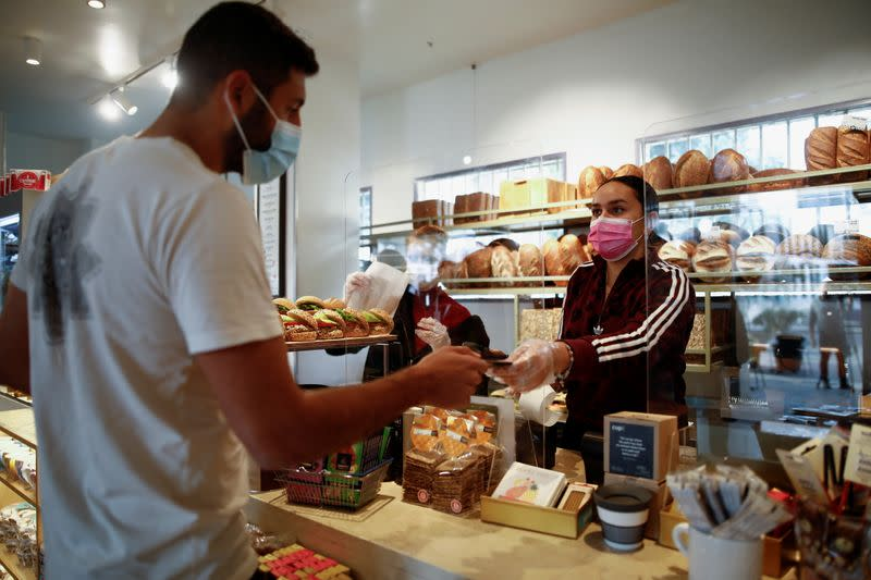 A customer pays at a cafe as Israel further eases the coronavirus disease (COVID-19) restrictions in Tel Aviv
