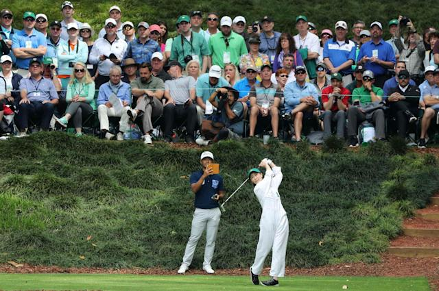 Satoshi Kodaira of Japan records his wife hitting off the 9th tee during the par 3 contest held on the final day of practice for the 2018 Masters golf tournament at Augusta National Golf Club in Augusta, Georgia, U.S. April 4, 2018. REUTERS/Lucy Nicholson