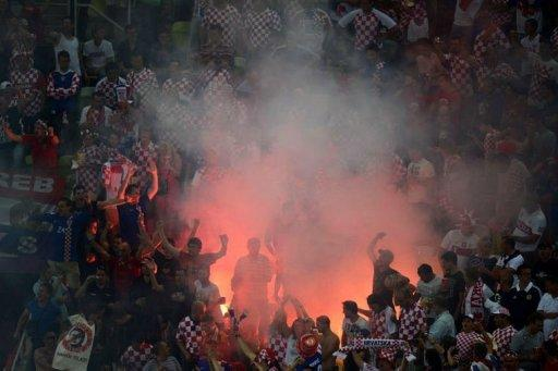 Fans of Croatia's national football team react as smoke billows from a flare at the match against Spain