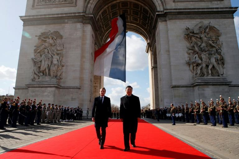 French President Emmanuel Macron, left, and Chinese President Xi Jinping laid a wreath before the eternal flame at the Arc de Triomphe in Paris on Monday