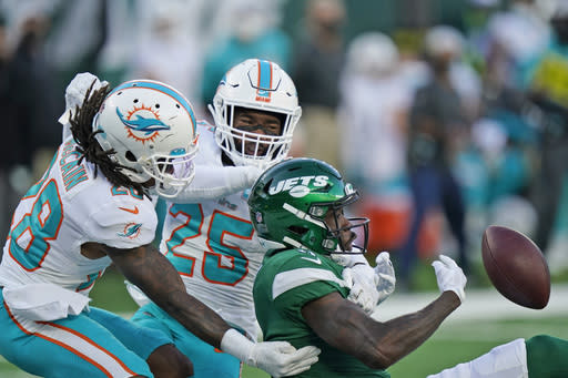 Miami Dolphins' Bobby McCain, left, and Xavien Howard, center, break up a pass intended for New York Jets' Denzel Mims, right, during the second half of an NFL football game, Sunday, Nov. 29, 2020, in East Rutherford, N.J. (AP Photo/Corey Sipkin)