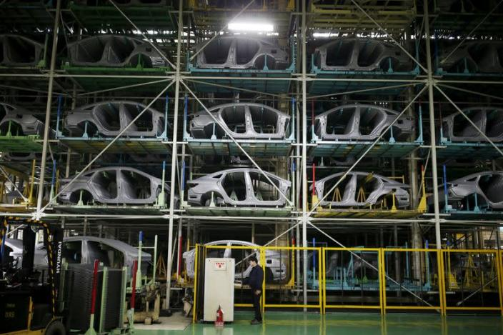 A worker stands in front of parts of Hyundai Motor's sedans at its plant in Asan