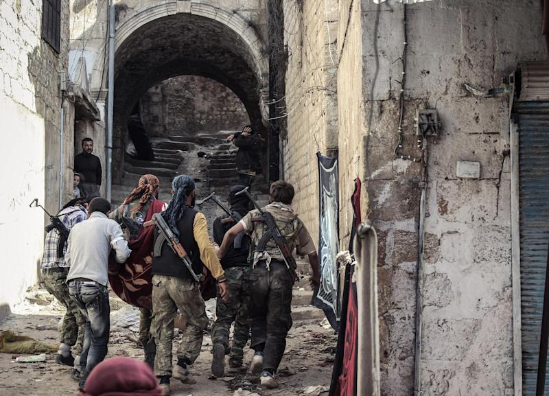 In this Tuesday, Oct. 30, 2012 photo, a group of Free Syrian Army fighters carry a wounded comrade to cover in the town of Harem, Syria. Despite two weeks of attacking a Roman-era citadel in which pro-Assad militia are dug in, the rebels failed to secure the town. (AP Photo/Mustafa Karali)