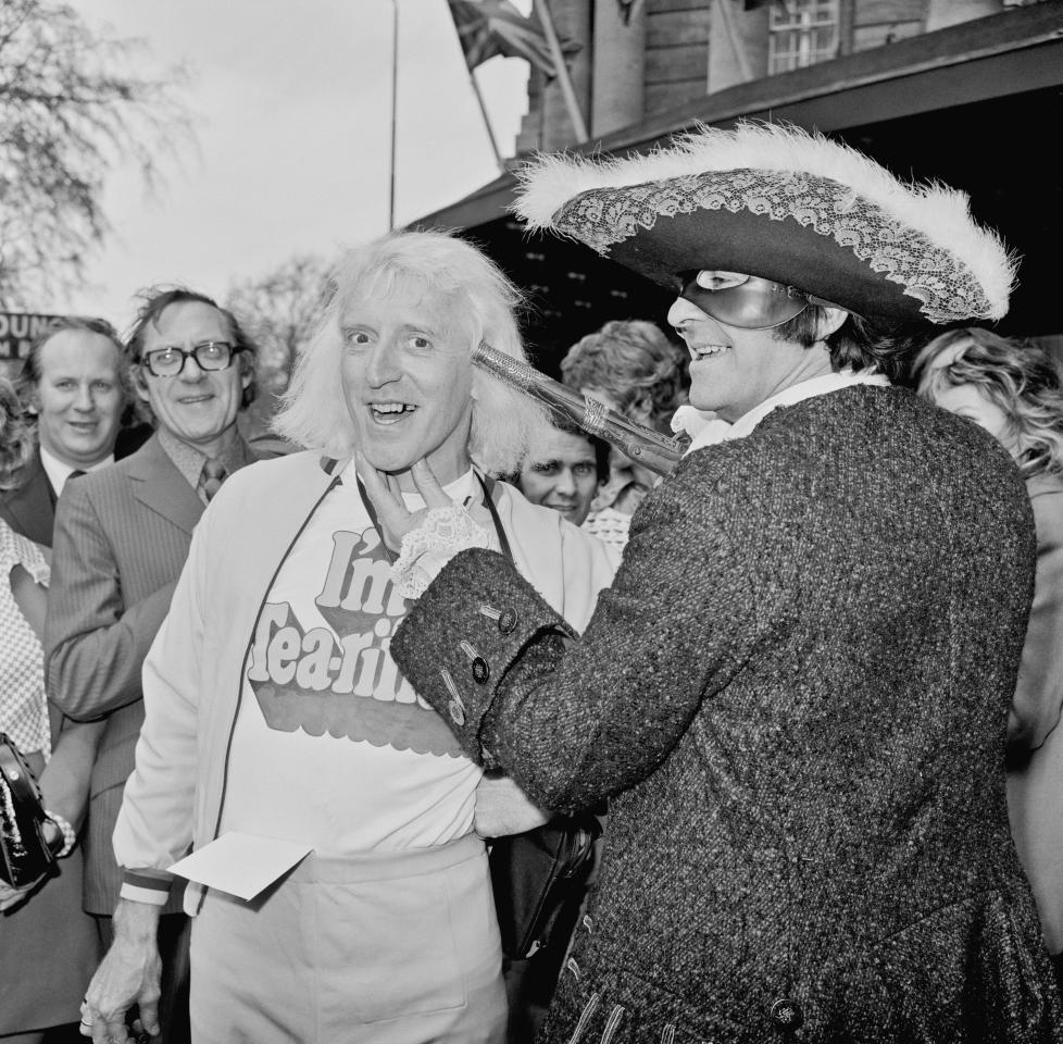 English television presenter Jimmy Savile (1926 - 2011) is held up by cricketer Fred Trueman (1931 - 2006) in the guise of a highwayman during a Variety Club of Great Britain charity walk luncheon, 19th April 1973. (Photo by Doug McKenzie/Getty Images)