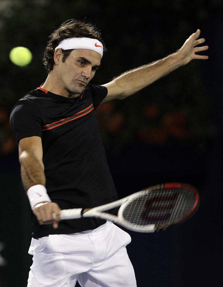Roger Federer of Switzerland returns the ball to Andy Murray of Britain during their final match at the Emirates Dubai ATP Tennis Championships in Dubai, United Arab Emirates, Saturday, March 3, 2012. (AP Photo/Hassan Ammar)